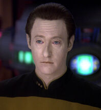 Screen cap of Brent Spiner as Data in his normal black and gold Starfleet uniform but with blue irises instead of yellow.